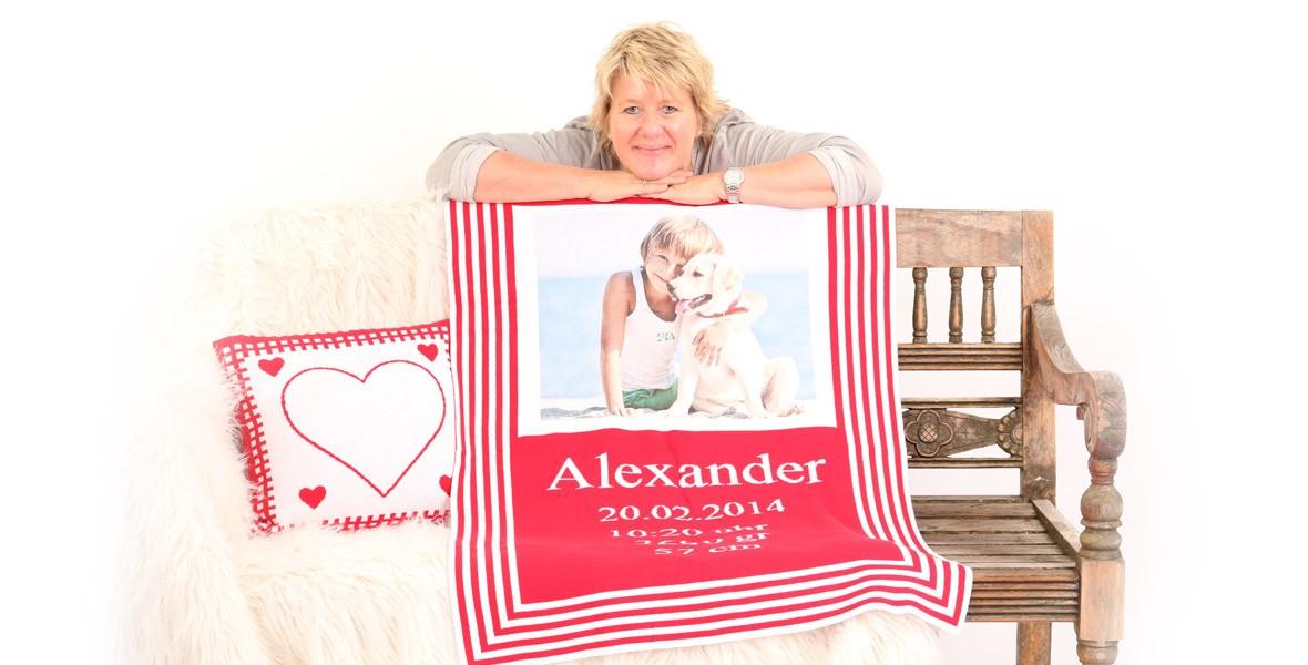 Beatrice Hauck, die Babydecke Gruenderin mit einer roten Babydecke und personalisiertem Kissen vor brauner Bank