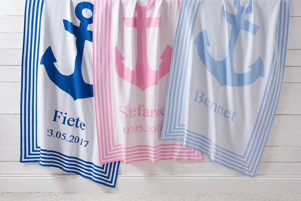 Drei hängende Babydecken in dunkelblau, rosa und hellblau mit Anker und Namen bestickt.