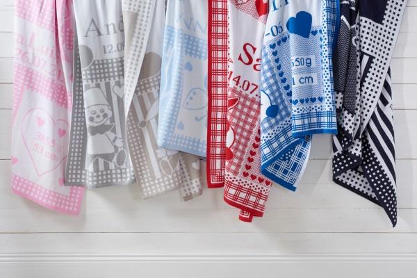 Sieben hängende, personalisierte Babydecken in verschiedenen Farben.