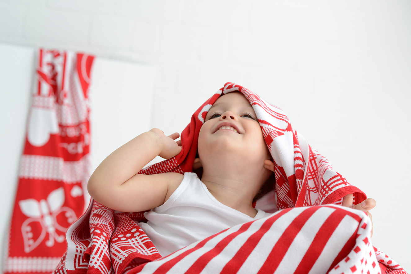 Grinsdender Junge hält sich eine rot-weiß gesteifte Babydecke über den Kopf.